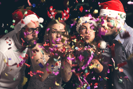 Two beautiful young couples wearing Santa hats, blowing away colourful confetti at midnight at New Years Eve party