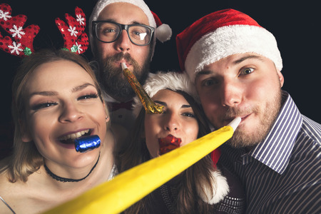 Two beautiful young couples wearing Santa hats, having fun at New Years party, dancing and blowing party whistles