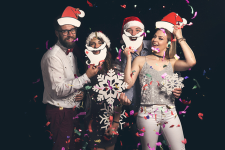 Two beautiful young couples having fun at New Years party, wearing Santa hats, holding cardboard snowflakes  and dancing