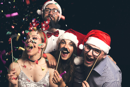 Group of young friends wearing Santa hats having fun at New Years Eve Party, posing for photos with masks Zdjęcie Seryjne
