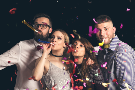 Two beautiful young couples having fun at New Years party, dancing and blowing party whistles
