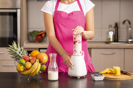Detail of woman making a fresh raspberry - banana smoothie in a blender; female hands holding a blender bowl while making smoothie