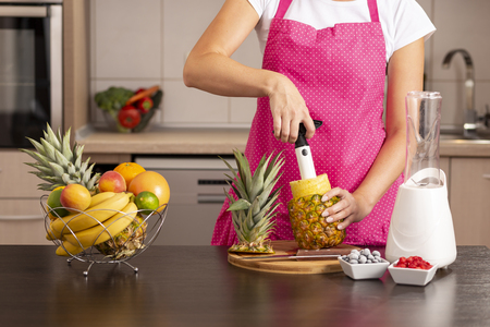Woman peeling a pineapple with a pineapple cutter, making a fresh, healthy, raw fruit smoothie Zdjęcie Seryjne