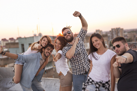 Group of young people having fun at a summertime rooftop party, at sunset. Focus on the couple in the middle Zdjęcie Seryjne