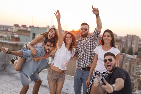Group of young people having fun at a summertime rooftop party, at sunset. Focus on the people on the left Zdjęcie Seryjne
