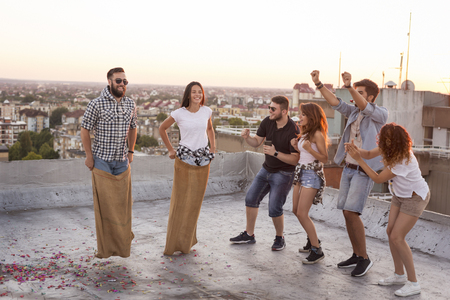Group of young people having fun at summertime rooftop party, cheering for their contestants in a sack race. Focus on the couple cheering on the left