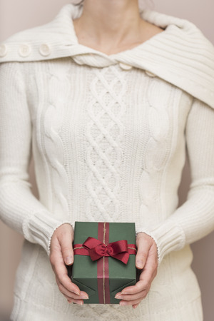 Detail of a young woman's hands holding a nicely wrapped present box. 版權商用圖片