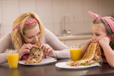 Mother and daughter having breakfast in the kitchen; daughter refuses to eat. Standard-Bild