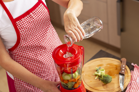 High angle view of female hands pouring water into a blender bowl over fresh vegetables for making vegetable broth. Focus on the water
