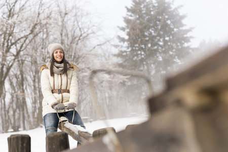 Beautiful young woman sitting on a seesaw, having fun and enjoying snowy winter day out