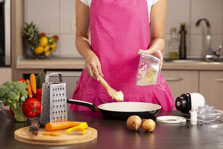 Detail of female hands putting chopped onion into a frying pan with a kitchen spoon from an onion chopper bowl on the kitchen counter Stock Photo