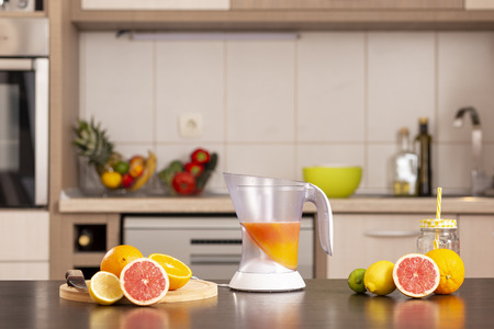 Fresh citrus fruit on a kitchen counter next to a citrus juicer Stockfoto