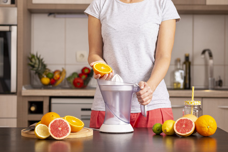 Detail of female hands making a freshly squeezed orange juice with the help of a citrus juicer on a kitchen counter