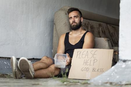 Homeless man sitting on the street, begging for money Stock Photo