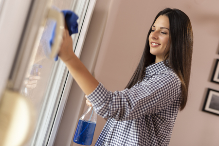 Beautiful young woman cleaning windows with a cleanser spray and a cloth; housekeeping assistant wiping windows