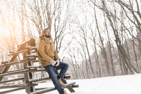 Handsome young man wearing a warm winter clothes, leaning against a wooden fence and enjoying a snowy winter day