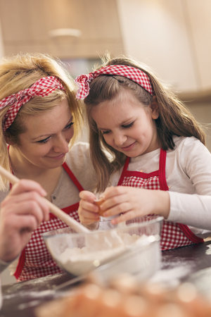 Young mother in the kitchen baking dough with her daughter; daughter adding an egg while mother is stirring the flour