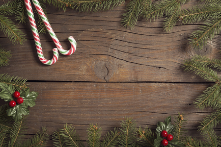 Top view of a frame made of pine branches and mistletoes with a candy canes placed on rustic wooden table