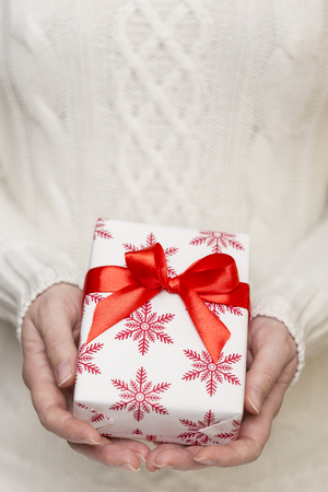 Detail of a young womans hands holding a nicely wrapped present box
