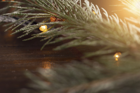 Detail of a snowy pine branch decorated with Christmas lights on a rustic wooden table. Selective focus on the branch Stockfoto
