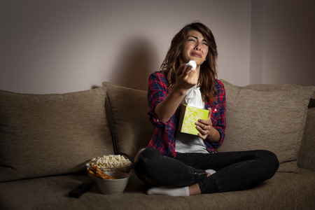 Beautiful young woman sitting in the dark on a living room couch, watching a soap opera and crying