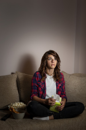 Beautiful young woman sitting in the dark on a living room couch, watching drama movie Imagens
