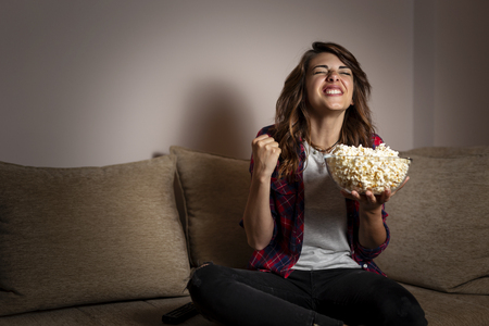 Beautiful young woman sitting in the dark on a living room couch, having fun watching a football match on TV and eating popcorn