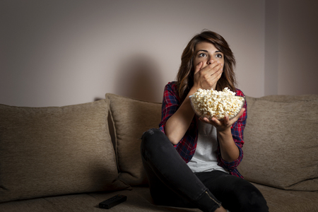 Beautiful young woman sitting in the dark on a living room couch, scared, watching a horror movie on TV and eating popcorn