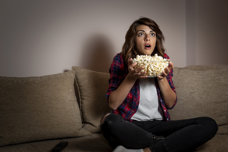 Beautiful young woman sitting in the dark on a living room couch, having fun watching TV and eating popcorn Stockfoto