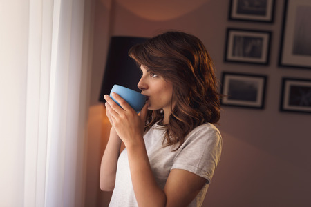 Beautiful young woman wearing pajamas, standing next to the living room window, drinking coffee