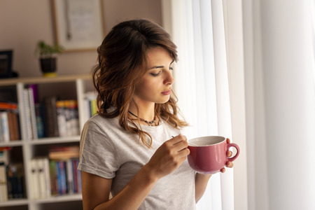 Beautiful young woman wearing pajamas, standing next to the living room window, holding a bowl of breakfast cereals and enjoying the weekend morning