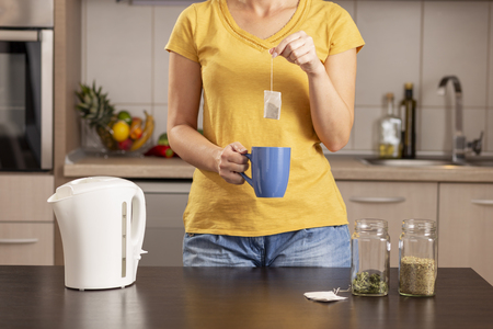 Woman making a cup of tea in the morning, holding  a cup and adding a teabag into a boiling water from a kettle Imagens