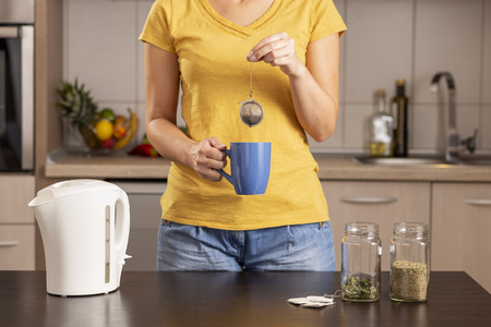 Woman making a cup of tea in the morning, holding  a cup and adding a bulk tea into a boiling water from a kettle Stockfoto