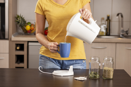 Woman making a cup of tea in the morning, pouring a boiling water from a kettle into a cup Stockfoto