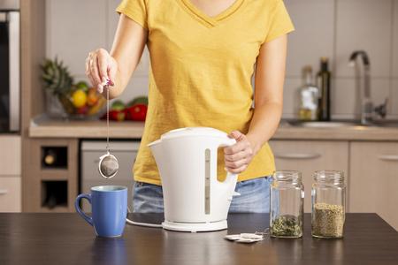 Donna che prepara una tazza di tè al mattino, tiene in mano un bollitore e aggiunge una bustina di tè in acqua bollente nella tazza da tè