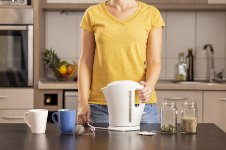 Woman making a cup of tea in the morning, holding a kettle filled with boiling water Stockfoto