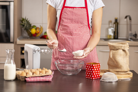 Detail of female hands adding flour into a mixing bowl while making a cake