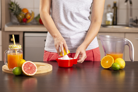 Detail of female hands holding half of lemon and squeezing it with lemon squeezer; woman making lemonade on a kitchen counter Stockfoto