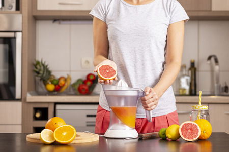 Detail of female hands holding a grapefruit half and making a freshly squeezed mixed citrus fruit with the help of a citrus juicer Stockfoto