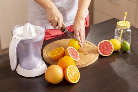 Detail of female hands holding a kitchen knife and cutting lemon on a cutting board; woman making a freshly squeezed mixed citrus fruit on a kitchen counter