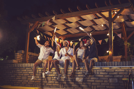 Group of young friends sitting on a poolside brick wall, having fun on a New Years Eve, dancing, drinking beer and waving with sparklers at midnight Stockfoto