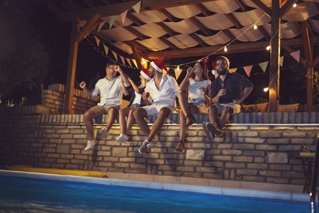 Group of young friends sitting on a poolside brick wall, having fun on a New Years Eve, dancing, drinking beer and blowing party whistles Stockfoto