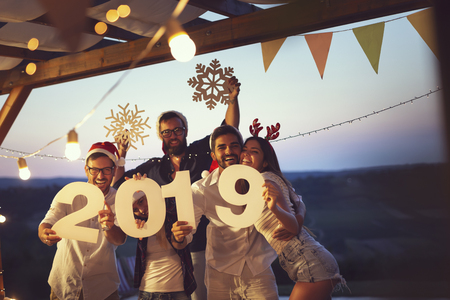 Group of young friends having fun at a New Years Eve outdoor pool party, dancing and holding cardboard snowflakes and numbers 2019. Focus on the couple on the right
