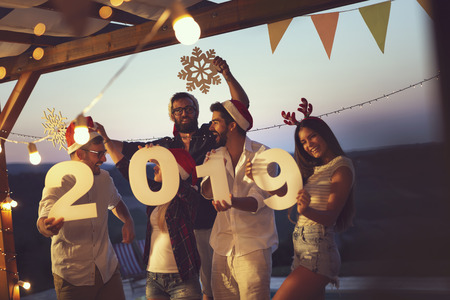 Group of young friends having fun at a New Years Eve outdoor pool party, dancing and holding cardboard snowflakes and numbers 2019. Focus on the men in the middle