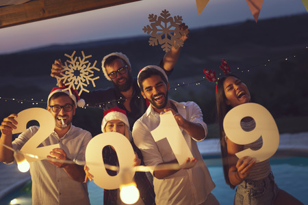 Group of young friends having fun at a New Years Eve outdoor pool party, dancing and holding cardboard snowflakes and numbers 2019