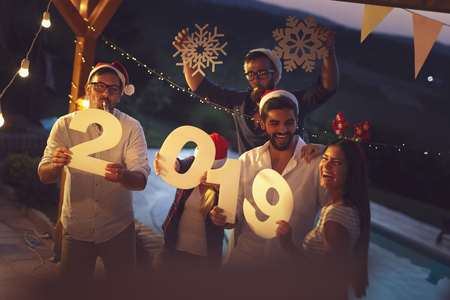 Group of young friends having fun at a New Years Eve outdoor pool party, dancing and holding cardboard snowflakes and numbers 2019. Focus on the men holding numbers
