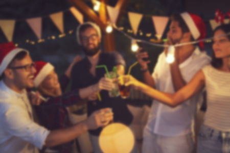 Group of young friends having fun at an outoodr poolside New Years Eve party, making a midnight countdown toast. Blurred people background
