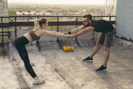 Young couple standing on a building rooftop terrace, holding hands and stretching before workout; urban skyline in the background