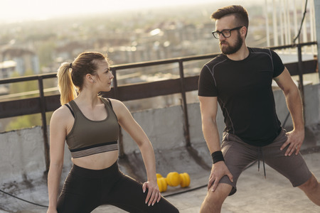 Young couple on a building rooftop terrace stretching before workout; urban skyline in the background. Focus on the girl