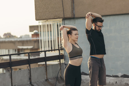 Couple standing on a building rooftop terrace, doing arms stretching exercises, urban skyline in the background. Focus on the girl